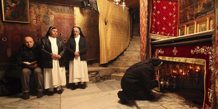 Peregrinos cristianos rezan dentro de la iglesia de la Natividad (Belén), en el punto donde nació Jesucristo.