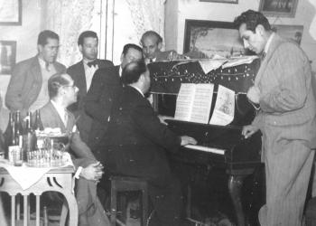 Benigno Ballón Farfán tocando el piano entre amigos y familiares en su sala de ensayo.