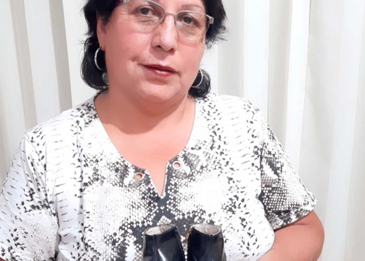 Doña Domitila muestra las botas que Justino hizo para su hija Melisa.