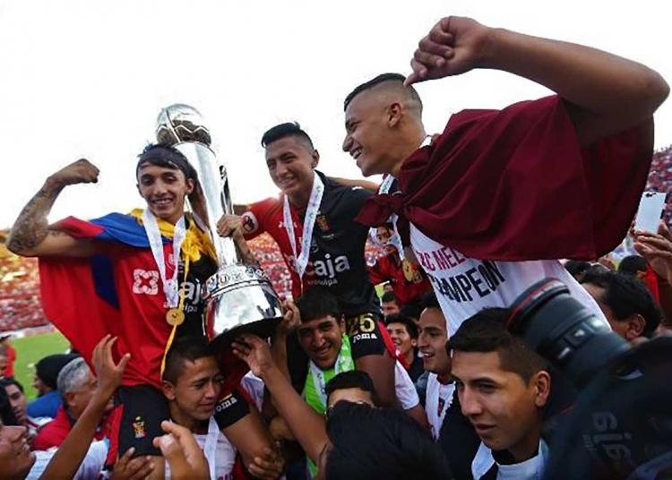 El joven futbolista, cargado en hombres, celebra el título junto a Omar Fernández y Patricio Arce.