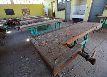 Las mesas donde antes se hacían clases de carpintería están deterioradas por el paso del tiempo.